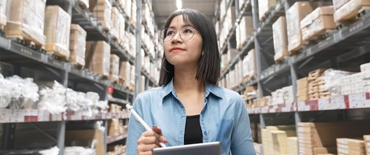 Candid photo of young asian woman auditor or trainee staff looking up at inventory while using retain accounting software on her computer tablet